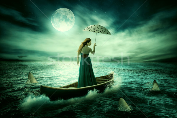 Young lonely woman with umbrella drifting on boat after storm surrounded by sharks Stock photo © ichiosea