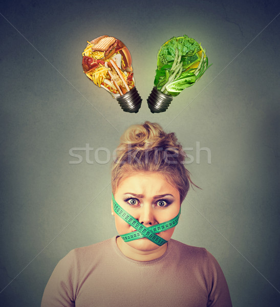 Diet restriction stress. Frustrated woman with measuring tape around her mouth   Stock photo © ichiosea