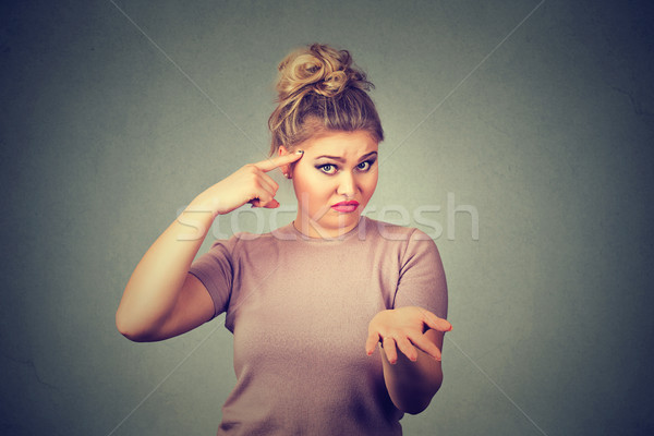 angry mad young woman gesturing with her finger against temple asking are you crazy? Stock photo © ichiosea