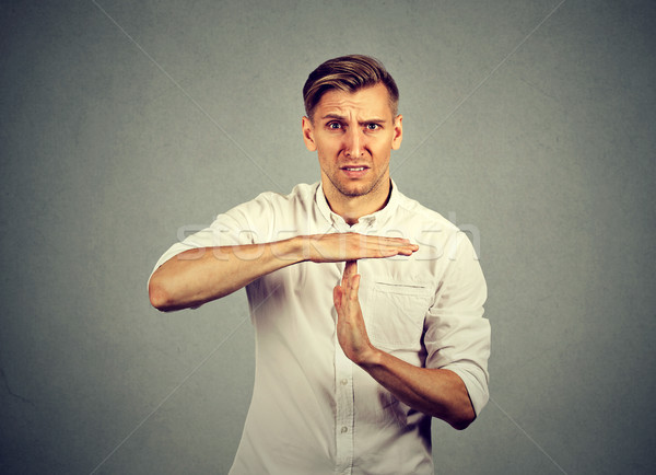 Young angry man showing time out hand gesture  Stock photo © ichiosea