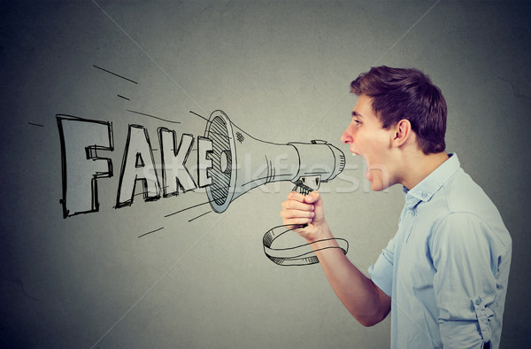 Stock photo: Side profile of a young man screaming in a megaphone spreading fake news