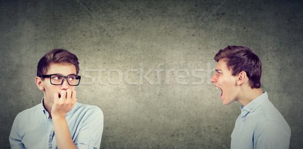 Split personality. Angry young man screaming at scared anxious himself Stock photo © ichiosea