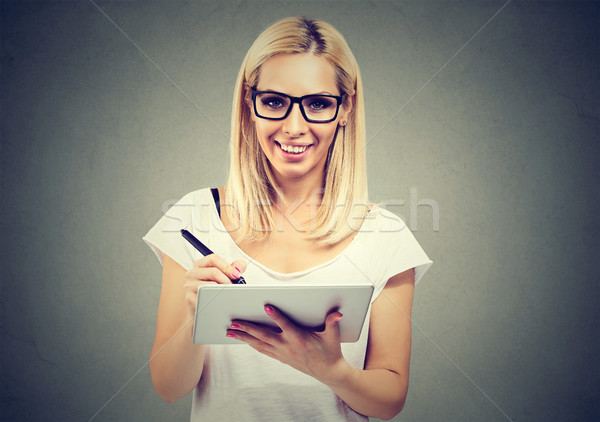 Closeup portrait of a young woman working with stylus and digital tablet pc Stock photo © ichiosea