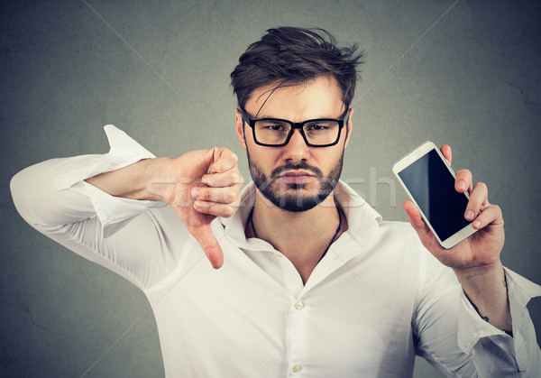 Man dissatisfied with quality of gadget mobile phone  Stock photo © ichiosea