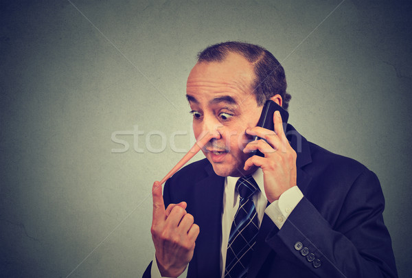 Liar customer service representative. Man with long nose talking on mobile phone lying  Stock photo © ichiosea