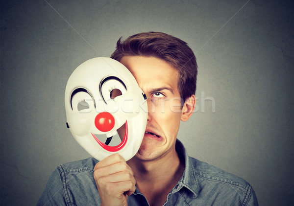 Upset frustrated angry man hiding behind happy face Stock photo © ichiosea