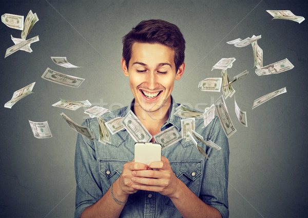 Stock photo: man using smartphone with dollar bills flying away from screen