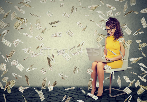 Stock photo: Young woman using a laptop building online business making money cash falling down
