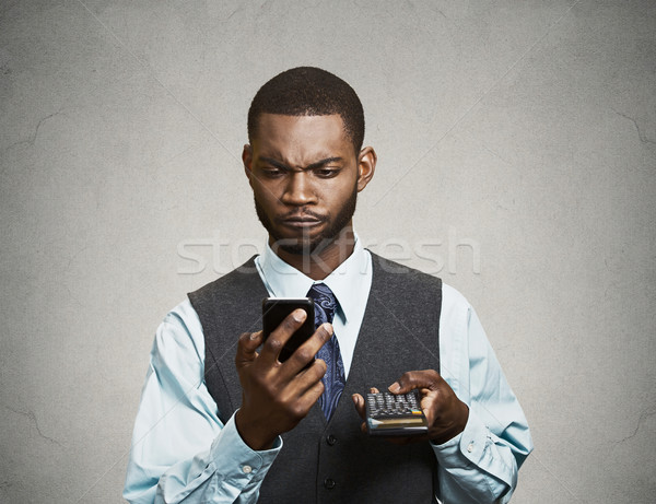 Corporate executive holding mobile phone and calculator Stock photo © ichiosea