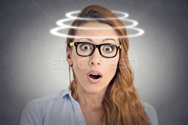 Stock photo: Head is spinning. Shocked woman with vertigo