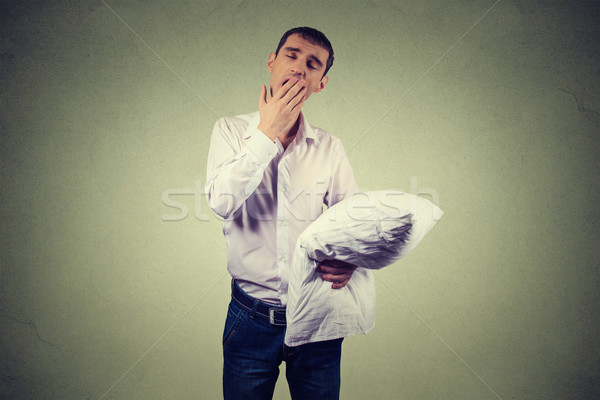 Handsome man yawning with a pillow in hand. Sleep deprivation, burnout Stock photo © ichiosea