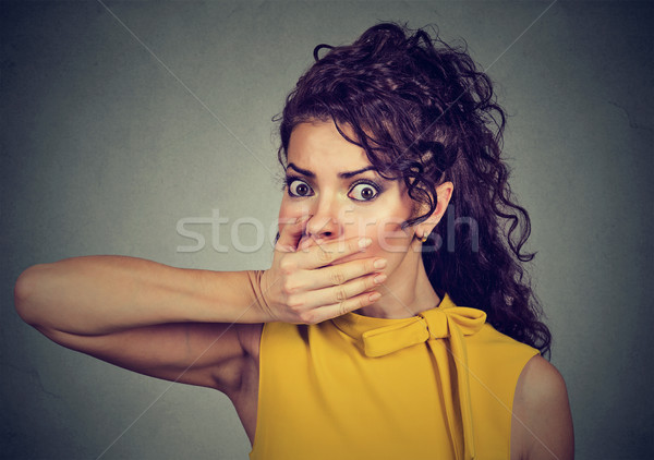 scared young woman covering with hand her mouth  Stock photo © ichiosea