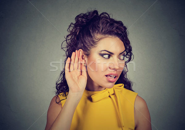 Curious woman with hand to ear secretly listening to gossip  Stock photo © ichiosea
