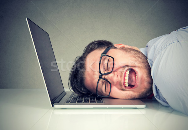 Stressed employee man sitting at desk with head on laptop feeling overworked and desperate  Stock photo © ichiosea