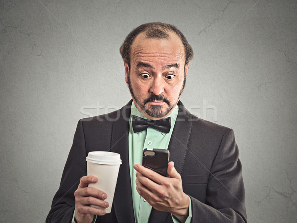 surprised man reading news on smartphone drinking coffee Stock photo © ichiosea