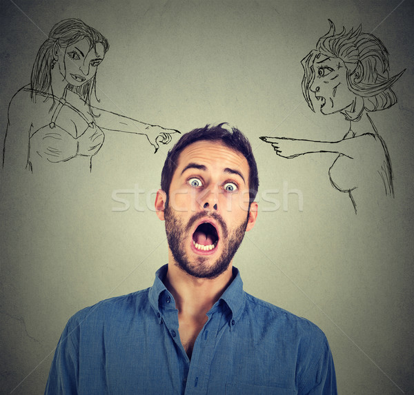 Two angry women blaming shocked scared young man   Stock photo © ichiosea