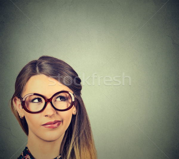 Stock photo: unny confused skeptical woman in glasses thinking planning looking up