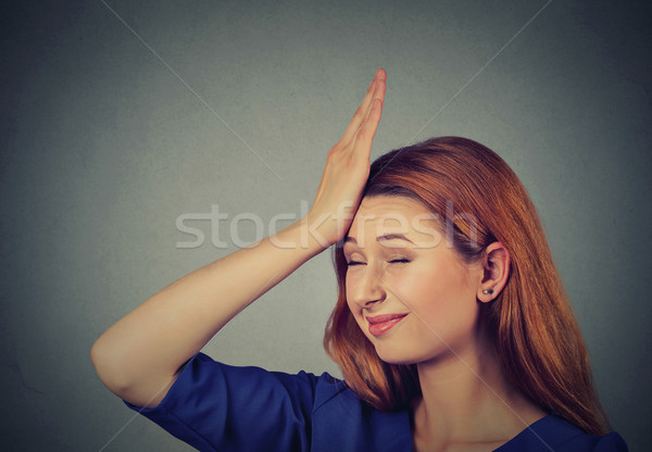 Regrets wrong doing. Silly young woman, slapping hand on head having duh  Stock photo © ichiosea