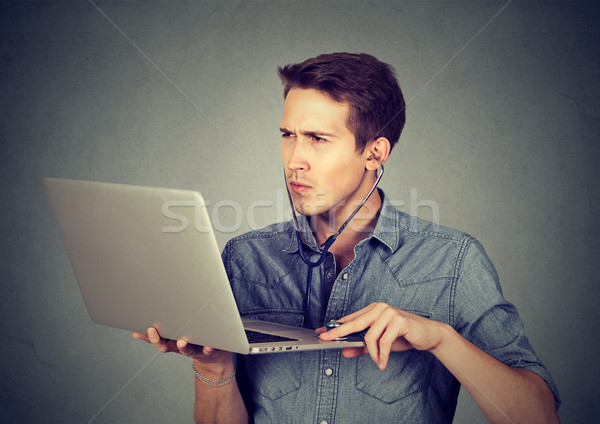 Man listening computer with stethoscope looking at pc laptop.  Stock photo © ichiosea