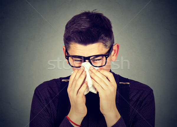 Man in glasses sneezing in a tissue blowing runny nose Stock photo © ichiosea