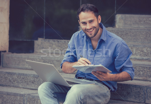 A handsome man sitting on steps with laptop and a notepad  Stock photo © ichiosea