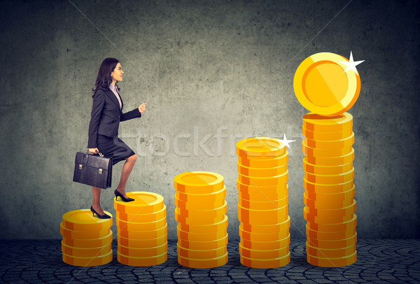 Business woman with briefcase stepping up a financial stairway ladder made of gold coins  Stock photo © ichiosea