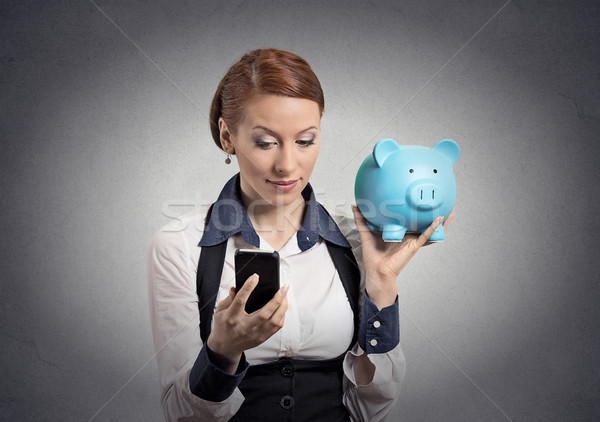 woman holding piggy bank looking at smart phone  Stock photo © ichiosea