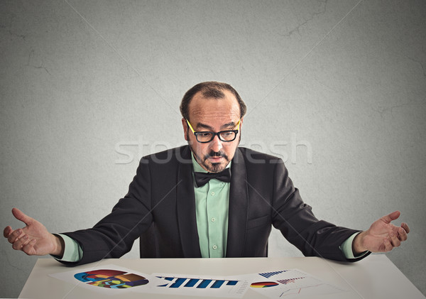 Stock photo: businessman sitting at table looking at financial reports