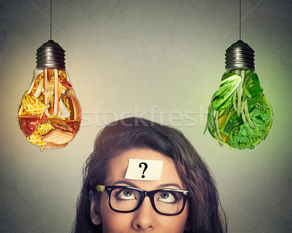 Woman thinking looking at junk food and vegetables shaped as light bulb  Stock photo © ichiosea