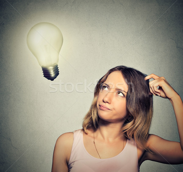 girl thinks looking up at bright light bulb Stock photo © ichiosea