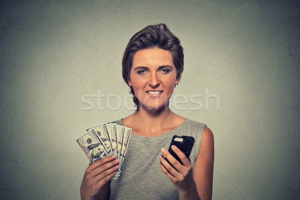 Excited woman with smart phone and dollar banknotes isolated on gray wall background  Stock photo © ichiosea