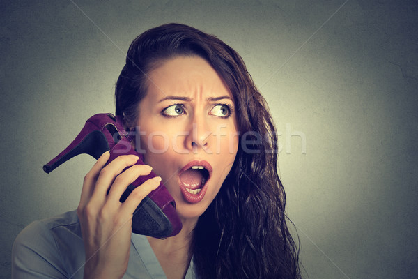 woman looking excited, surprised holding high heeled shoe in her hand as phone Stock photo © ichiosea