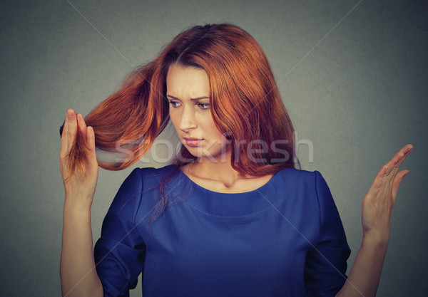 upset frustrated young woman surprised she is losing hair, noticed split ends  Stock photo © ichiosea