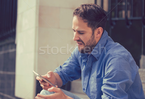 Angry man looking at mobile phone sitting on steps outside apartment complex  Stock photo © ichiosea
