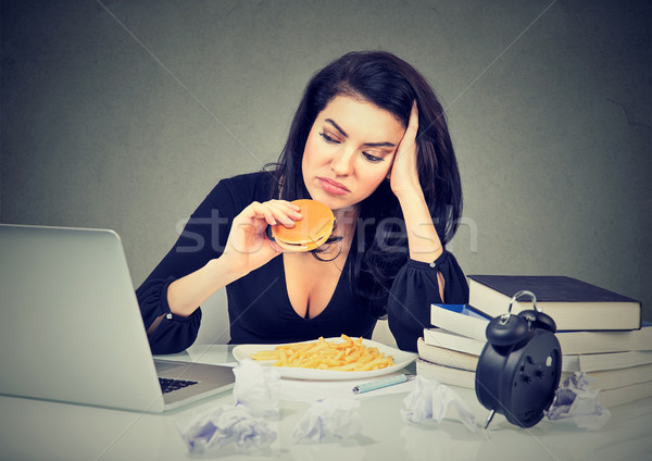 Sedentary lifestyle and junk food concept. Stressed woman sitting at desk eating hamburger Stock photo © ichiosea