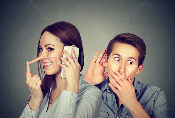 Cheating girlfriend. Man listening to a woman liar talking on mobile phone with her lover  Stock photo © ichiosea