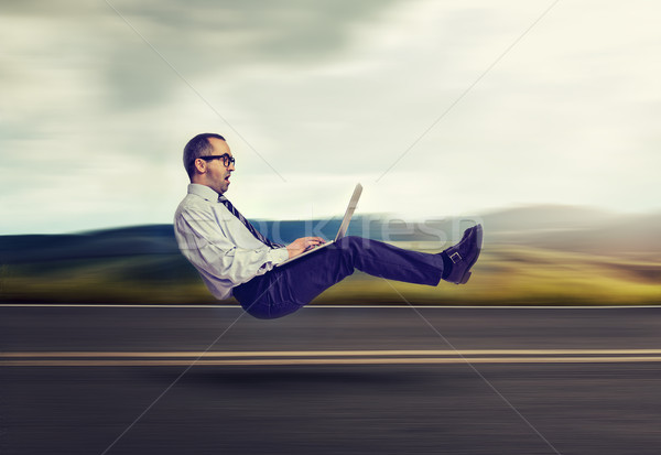 Fast internet concept. Levitating business man on road using laptop computer  Stock photo © ichiosea