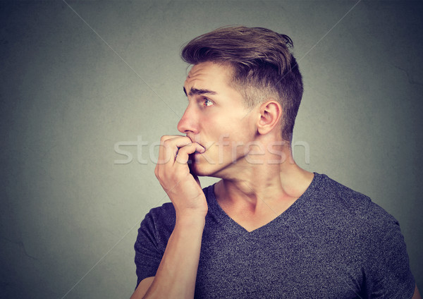 Preoccupied anxious young man biting his fingernails looking to the side  Stock photo © ichiosea