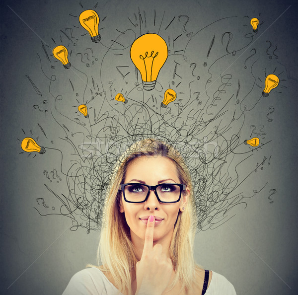 Brain connections. Happy thoughtful woman looking up at many ideas light bulbs above head. Stock photo © ichiosea