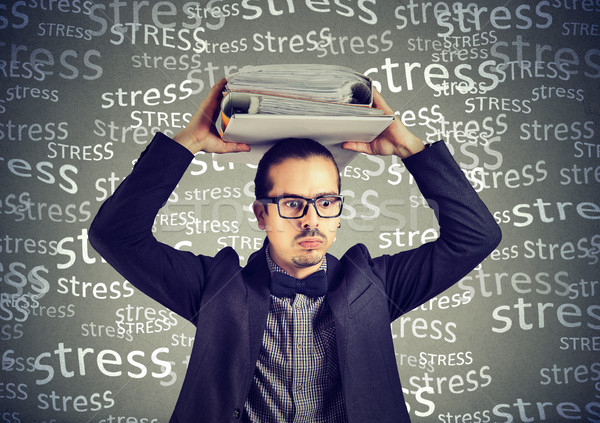 Stressed doomed business man standing with heavy folders on his head  Stock photo © ichiosea