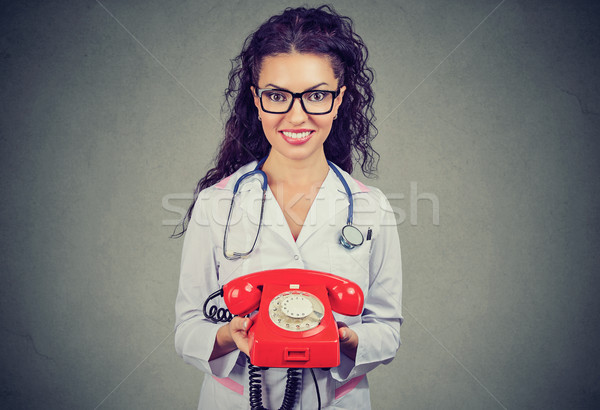 Smiling female doctor holding a telephone ready to answer phone calls Stock photo © ichiosea