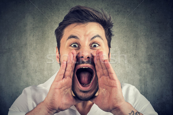 Closeup of upset, angry man with hands close to wide opened mouth yelling Stock photo © ichiosea