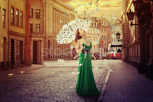 Stock photo: woman with umbrella under a money rain