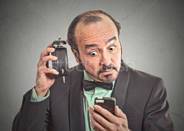 man with alarm clock looking at his smart phone Stock photo © ichiosea