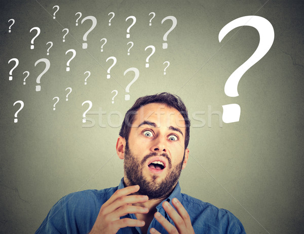 Surprised funny looking scared business man with many question marks  Stock photo © ichiosea