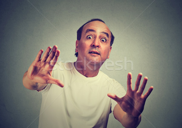 Man scared with shocked facial expression trying to protect himself from unpleasant situation Stock photo © ichiosea