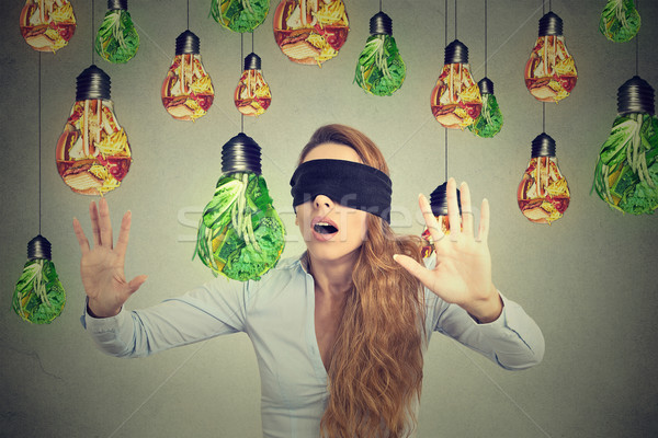 Blindfolded woman walking through light bulbs shaped as junk food green vegetables Stock photo © ichiosea