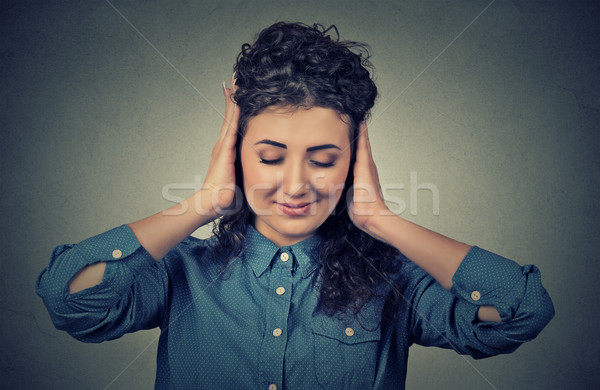 Headshot beautiful young woman covering both ears with her hands  Stock photo © ichiosea