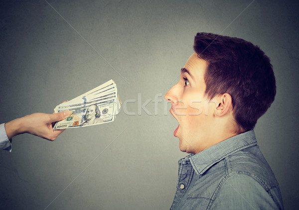 Shocked surprised man looking at offered cash dollar bills  Stock photo © ichiosea