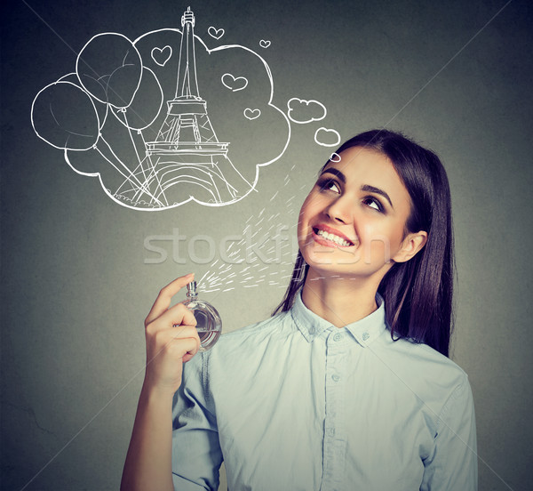 Beautiful woman holding bottle of perfume and smelling aroma  Stock photo © ichiosea